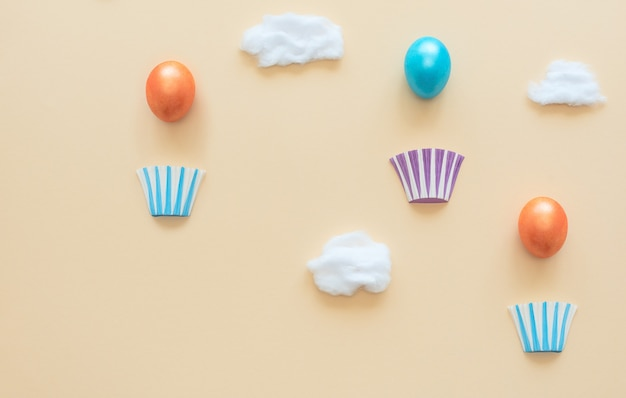 Hot air balloons made of decorated easter eggs with baskets on yellow with clouds