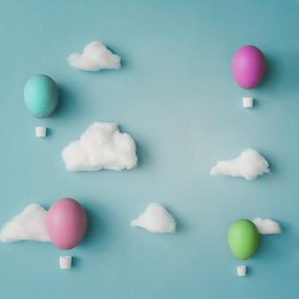 밝은 파란색 표면에 면화 구름 장식 된 부활절 달걀로 만든 뜨거운 공기 풍선