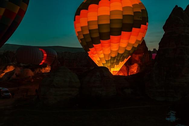 Hot air balloons at sunrise preparing for flight.