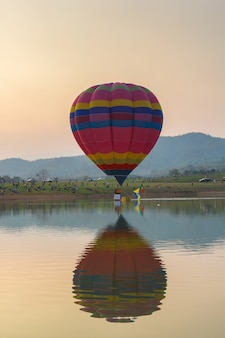 Hot air color balloon over lake with sunset time, chiang rai province, thailand