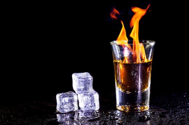 Горячий алкогольный коктейль горит в рюмке с кубиками льда.