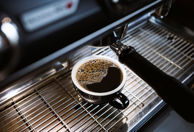 Горячий американо на кофеварке в кафе с софт-фокусом и засветкой на заднем плане