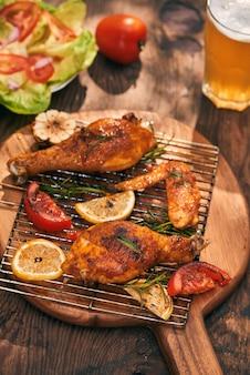 Горячие и пряные куриные голени и крылышки крупным планом с пивом