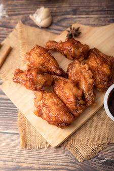 Горячая и пряная жареная курица по-корейски на деревянной разделочной доске
