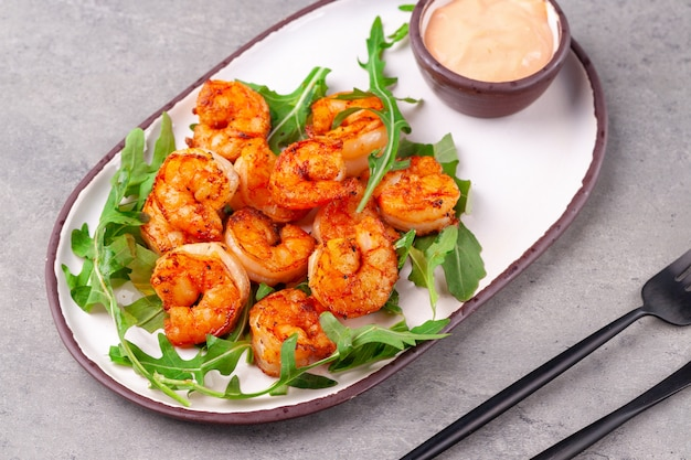 Hot appetizer fried king shrimps, arugula, sauce