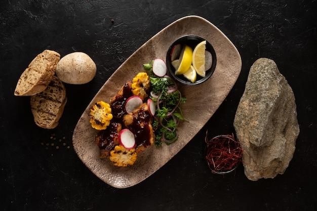 鶏肉の切り身、焼きトウモロコシ、野菜を使った温かい前菜。
