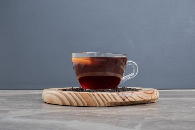 Горячий ароматный чай на деревянной тарелке на мраморном столе.