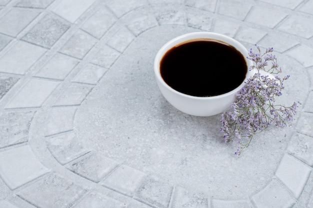 Tè caldo e aromatico con fiori su superficie bianca.
