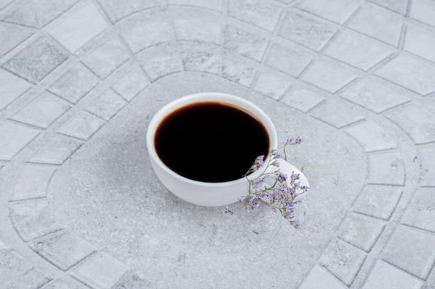 Tè caldo e aromatico con fiori su fondo bianco.