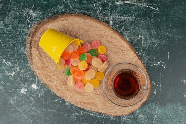 Tè caldo, aroma con bollitore e caramelle di gelatina su tavola di legno.