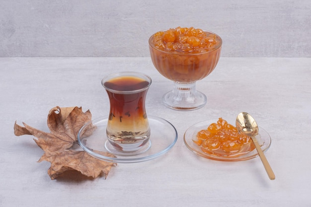 Hot aroma tea with leaves and jam on white table.