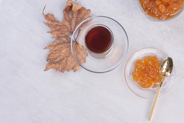Tè aromatico caldo con foglie e marmellata sul tavolo bianco.