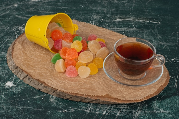 Hot, aroma tea with yellow bucket of jelly candies on wooden board