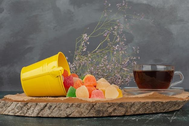Горячий ароматный чай с желтым ведром желейных конфет на деревянной доске