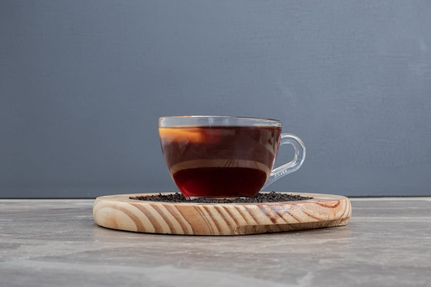 Hot, aroma tea on wooden plate on marble table.