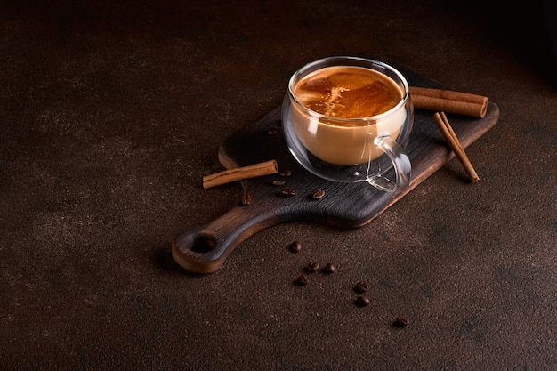 Hot and aromatic coffee spilling from glass cup on the dark background. concept of tasty refreshment beverage with coffee. copy space for text, menu or recipe