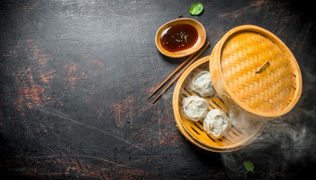 Hot aromatic manta dumplings in bamboo steamer with soy sauce on dark rustic table