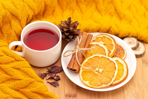 Hot aromatic tea with cinnamon sticks and slices of dried oranges. on a wooden table