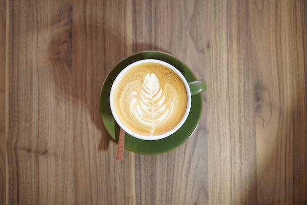 Горячий арт-латте в зеленой чашке на деревянном столе