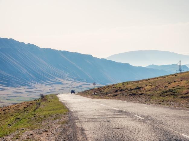 丘や山々を通る熱いアスファルト道路。空の山道をオンにします。ダゲスタンの古いひびの入ったアスファルト山道。