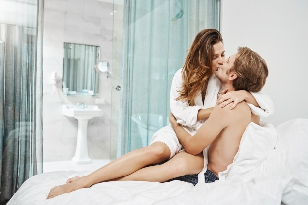 Hot attractive girlfriend sits on boyfriend while kissing and hugging him tenderly in bed. foreplay moment of two people in relationship, spending time in hotel room that fills with sexual tension.