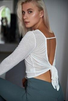 壁に向かって熱い魅力的な女性。部屋の窓の近くでポーズをとるセクシーなブロンドの女の子。