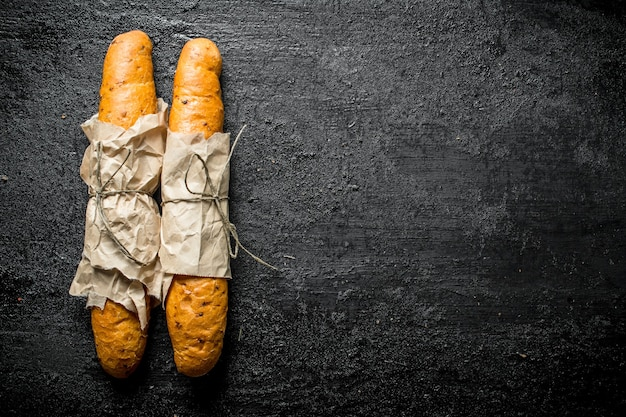 Hot baguette in paper. on black rustic surface