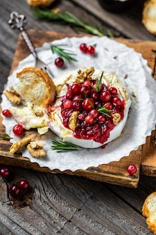 Hot baked camembert with fresh rosemary, cranberry sauce and baguette bread on wooden table.