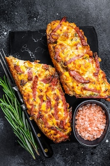 Hot baked open baguette sandwich with ham, bacon, vegetables and cheese. black background. top view.