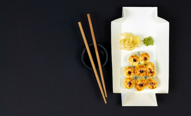Hot baked sushi rolls in eco disposable box top view on dark background.