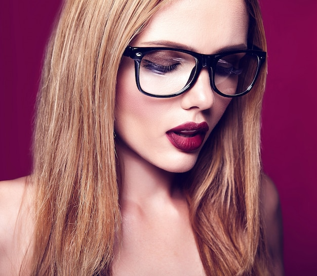 Hot beautiful blond woman model with fresh daily makeup with dark lips color and clean healthy skin on red background in glasses