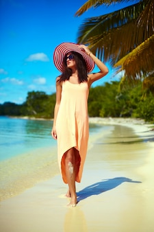 Hot beautiful woman in colorful sunhat and dress walking near beach ocean on hot summer day near palm
