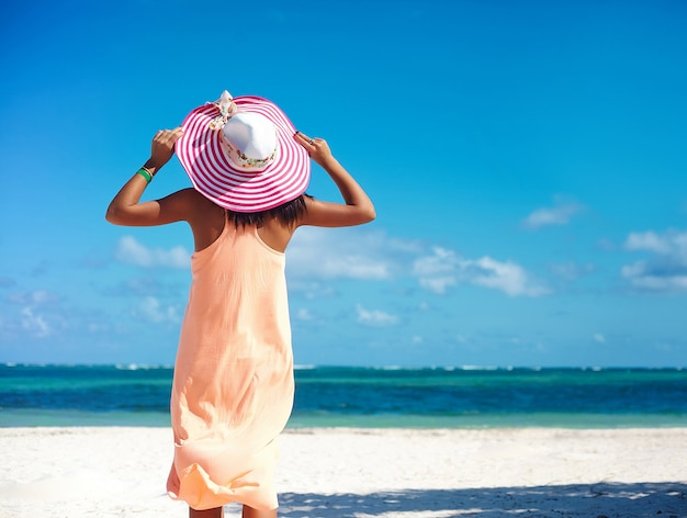 Hot beautiful woman in colorful sunhat and dress walking near beach ocean on hot summer day on white sand
