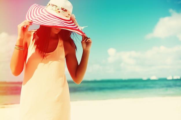 カラフルなsunhatと白い砂の上の夏の暑い日にビーチの海の近くを歩いてドレスのホット美しい女性