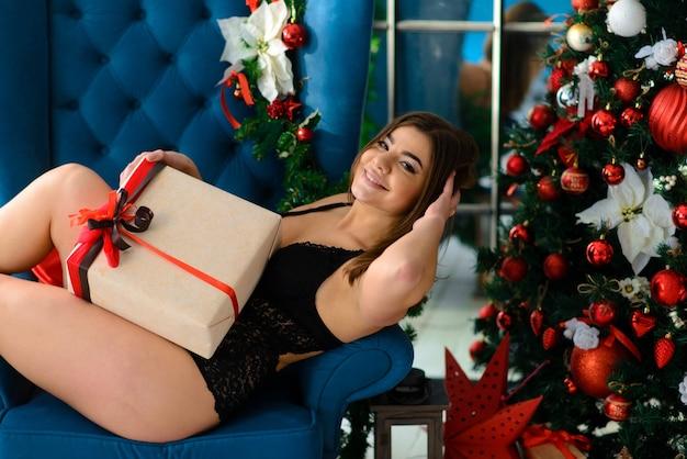 暖炉のそばでポーズをとるレースの黒いランジェリーでホットな美しい女性。クリスマスのインテリア。官能的な女の子。
