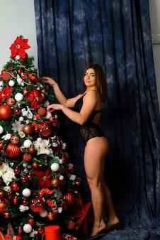 벽난로 근처 포즈 레이스 검은 란제리에 뜨거운 아름 다운 여자. 크리스마스 인테리어. 관능적 인 소녀.
