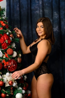 Hot beautiful woman in lacy black lingerie posing near the fireplace. christmas interior.