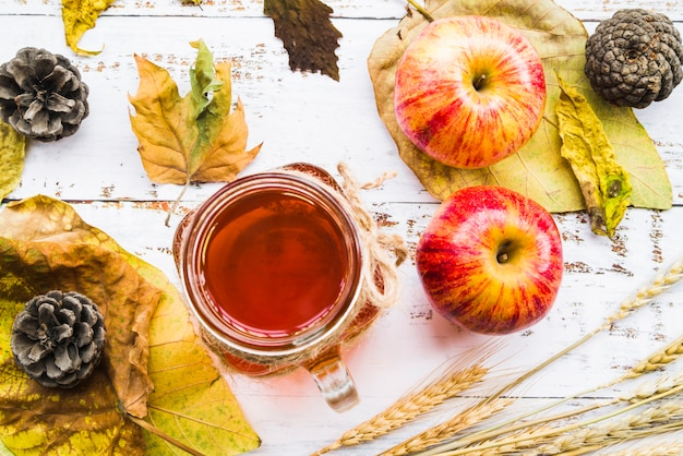 Hot beverage among leaves and apples