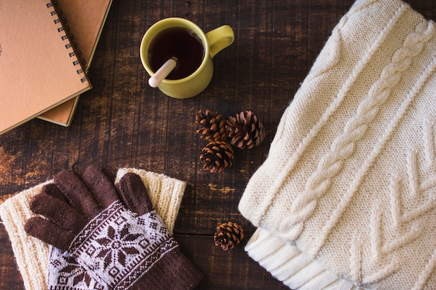 Hot beverage and cones near notebook and knitted clothes