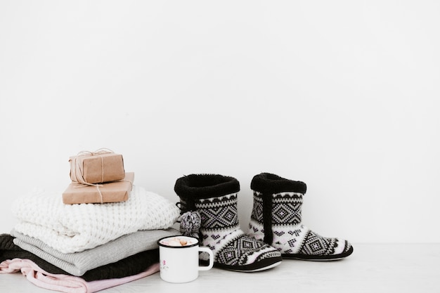 Hot beverage and presents near warms apparels