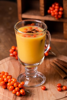 Hot beverage of sea-buckthorn berries in glass cup. rustic style.