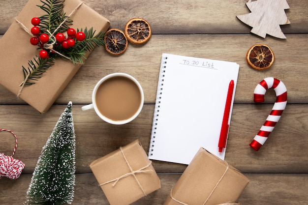 Hot beverage with notebook and christmas gifts