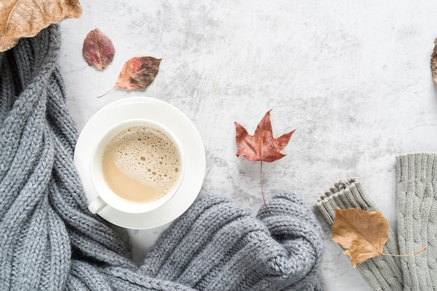 Hot beverage with warm sweater on light surface