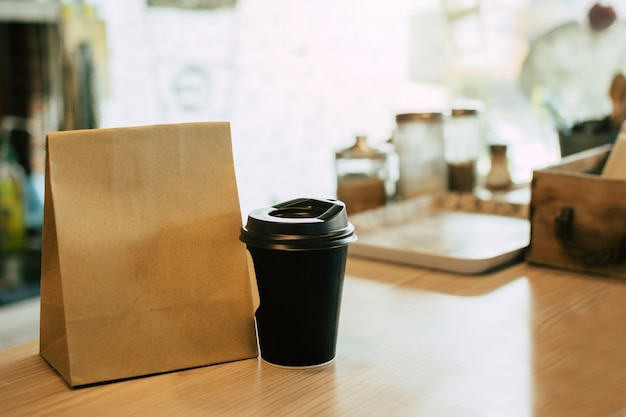 Hot black coffee cup and dessert paper set bag waiting for customer on counter in modern cafe coffee shop, food delivery, cafe restaurant, takeaway food, small business owner, food and drink concept