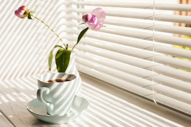 Hot black coffee and vase of flowers on windowsill