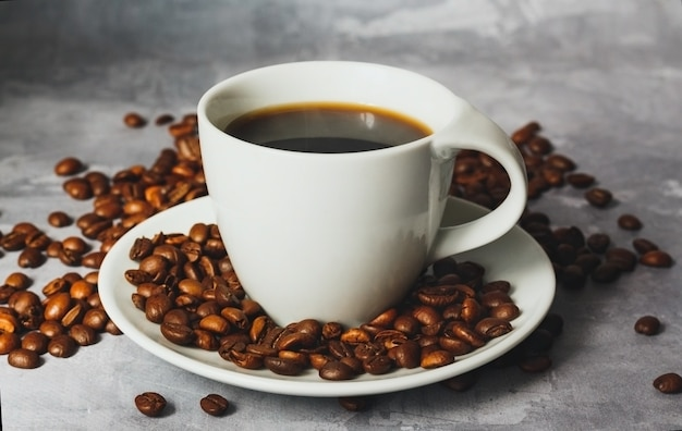 Hot black coffee in white ceramic cup with coffee beans around on textured grey background