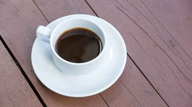 Hot black coffee in a white cup on a wooden table.