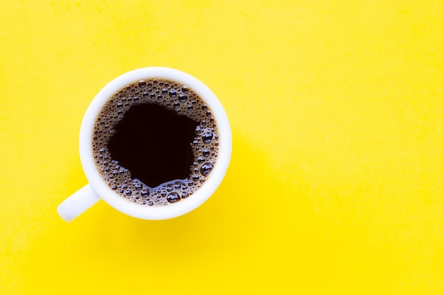Hot black coffee on  yellow surface.