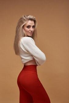 茶色でポーズをとって赤いズボンの熱いブロンドの女の子