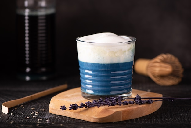 Hot blue matcha with latte foam in a small glass